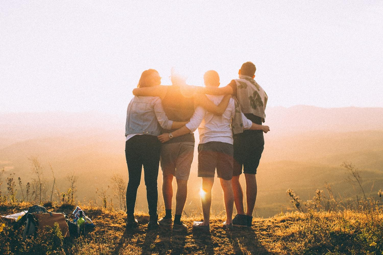 Przyjaciele przytulający się przy zachodzie słońca