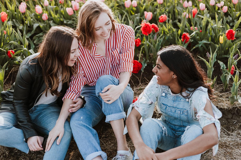 Trzy przyjaciółki śmiejące się na polu tulipanów